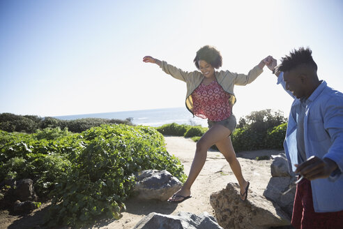 Playful young couple on rocks on sunny beach - HEROF26651