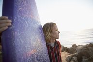 Pensive male surfer holding surfboard on beach - HEROF26657