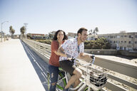 Playful couple laughing on bicycle on sunny California bridge - HEROF26666