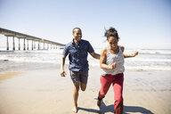 Playful couple running on sunny beach - HEROF26675