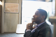 Pensive, attentive African American businessman listening in office - HEROF26690