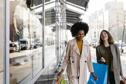 Two happy women with shopping bags walking in the city - JRFF02759