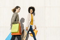 Two happy women with shopping bags walking along a wall - JRFF02765