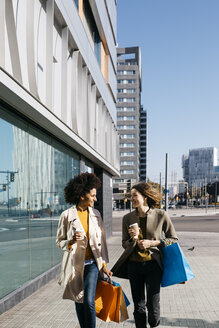 Two happy women with shopping bags and takeaway coffee walking in the city - JRFF02774