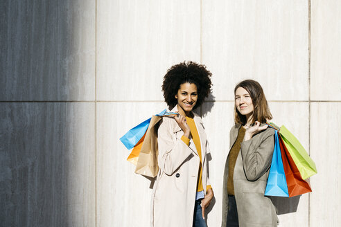 Portrait of two happy women with shopping bags standing at a wall - JRFF02777