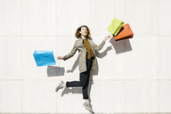 Cheerful woman with shopping bags jumping at a wall - JRFF02783