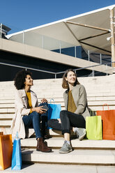 Two happy women with shopping bags sitting on stairs - JRFF02789