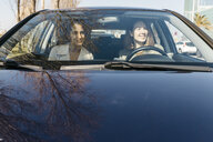 Two women driving in a car through the city - JRFF02792
