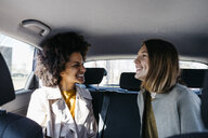 Two happy women sitting in back seat of a car - JRFF02801