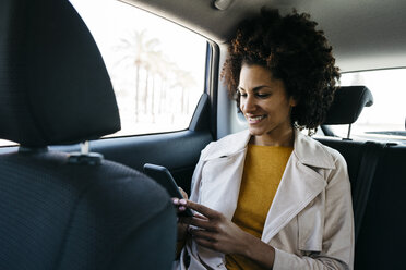 Smiling woman sitting in back seat of a car using cell phone - JRFF02804