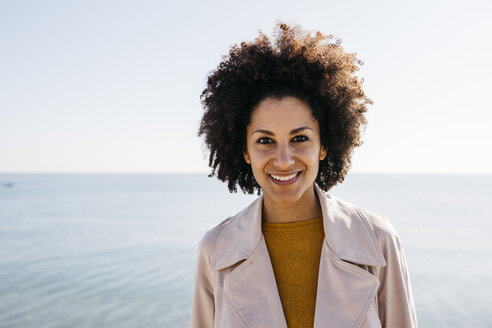 Portrait of smiling woman with the sea in background - JRFF02813