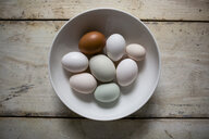 Overhead view of eggs in bowl on wooden table - CAVF62096