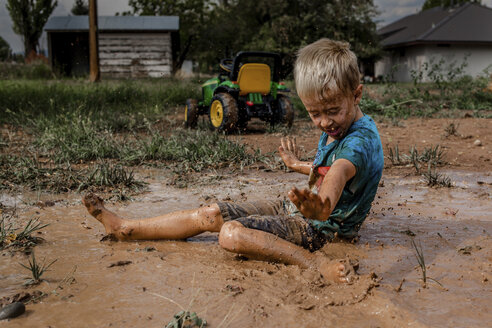 Side view of playful boy with arms outstretched sitting on muddy puddle in yard - CAVF62207