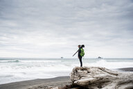 Side view of male hiker standing on log at beach against cloudy sky in Olympic National Park - CAVF62216