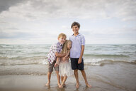 Full length of playful siblings standing on shore at beach - CAVF62222