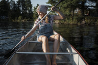 Happy woman rowing boat on lake at Algonquin Provincial Park - CAVF62291