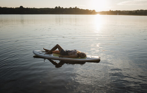 High angle view of woman lying on paddleboard in lake against sky during sunset - CAVF62294
