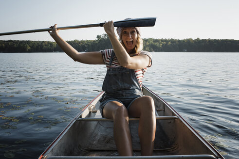 Portrait of happy woman with mouth open holding oar while sitting in boat on river against sky - CAVF62303