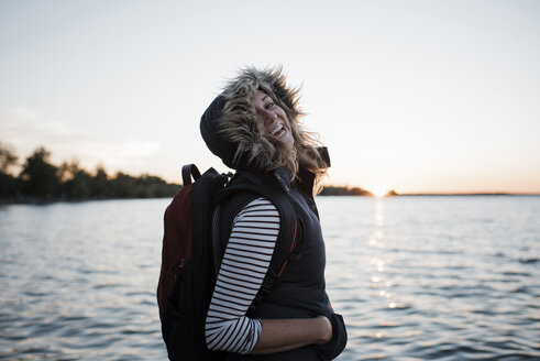 Portrait of happy woman with backpack standing at lakeshore against clear sky during sunset - CAVF62309