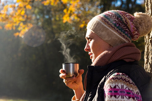 Woman having warm drink in autumnal forest - CUF49268