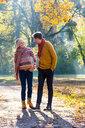 Couple walking in autumnal park, Strandbad, Mannheim, Germany - CUF49274