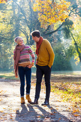 Couple walking in autumnal park, Strandbad, Mannheim, Germany - CUF49274
