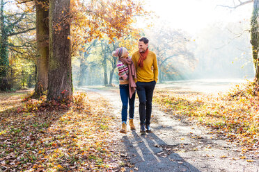 Couple walking in autumnal park, Strandbad, Mannheim, Germany - CUF49277