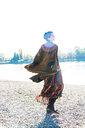 Woman twirling by Rhine River, Strandbad, Mannheim, Germany - CUF49283