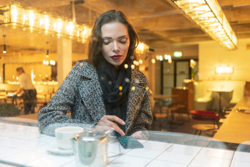 Young woman using smartphone in cafe, London, UK - CUF49292