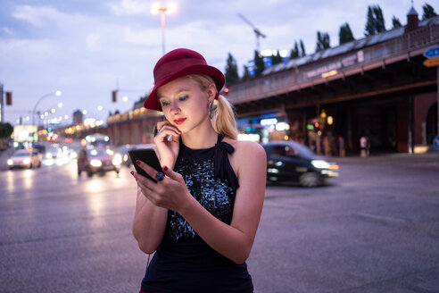 Hipster woman texting in street, Berlin, Germany - CUF49298