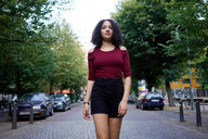 Young woman in middle of street, Berlin, Germany - CUF49319