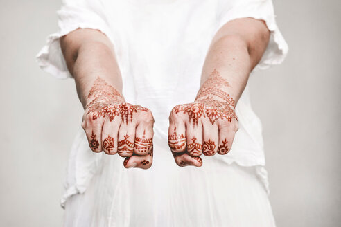 Woman in white dress with henna tattoo on fists - CUF49352