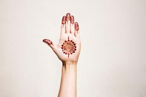 Hand with henna tattoo making gesture - CUF49355