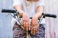 Woman with henna tattoo on hands sitting on bicycle - CUF49358
