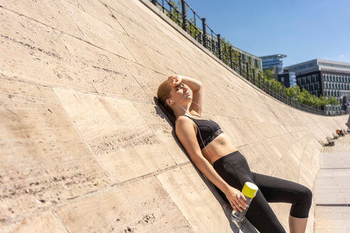 Young woman taking break from exercise in city, Berlin, Germany - CUF49364