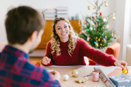 Couple preparing Christmas decorations at home - CUF49421
