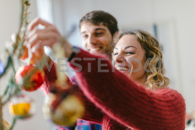 Couple decorating Christmas tree at home - CUF49424