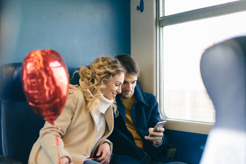 Couple with heart shaped balloon using smartphone inside train - CUF49445