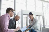Business people reviewing paperwork in lobby - HEROF26741