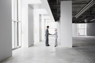 Businessman and businesswoman handshaking in empty office - HEROF26753