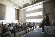 Audience watching female cellist perform on auditorium stage - HEROF26795