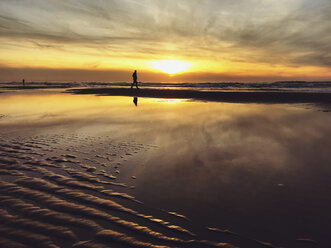 Belgium, Flanders, North Sea Coast, man walking along tide pool watching sunset and ocean waves, listening to the ocean sounds - GWF05906