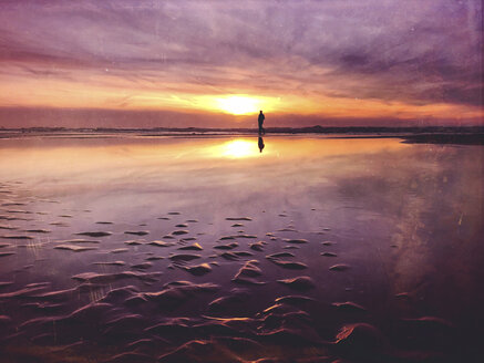 Belgium, Flanders, North Sea Coast, man walking along tide pool watching sunset and ocean waves, listening to the ocean sounds - GWF05912