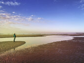 Belgium, Flanders, North Sea, Coast, woman standing on beach insunset light, relaxing and listening to oceansounds - GWF05915