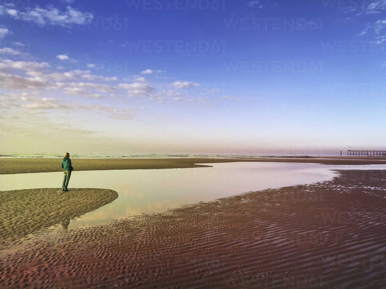 Belgium, Flanders, North Sea, Coast, woman standing on beach insunset light, relaxing and listening to oceansounds - GWF05915 - Gaby Wojciech/Westend61