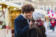 Happy affectionate young couple at Christmas market - MGIF00312