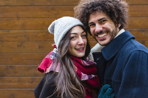 Portrait of happy young couple in winterwear in front of wooden wall - MGIF00315