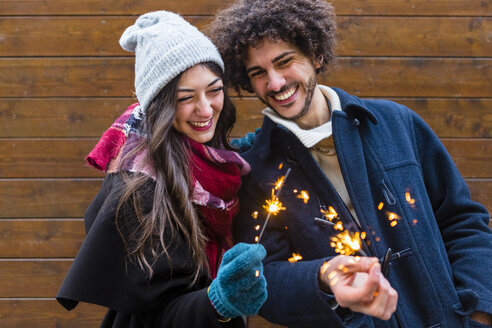Happy young couple in winterwear holding sparklers in front of wooden wall - MGIF00318