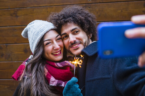 Happy young couple in winterwear holding sparkler and taking a selfie in front of wooden wall - MGIF00321