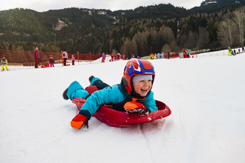 Italy, Trentino-Alto Adige, happy boy on tobogganing plastic sledge - MGIF00323